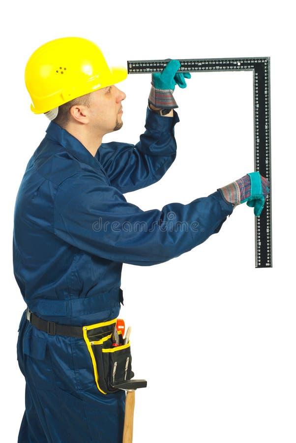 De mens van de bouwer maakt meting royalty-vrije stock afbeeldingen