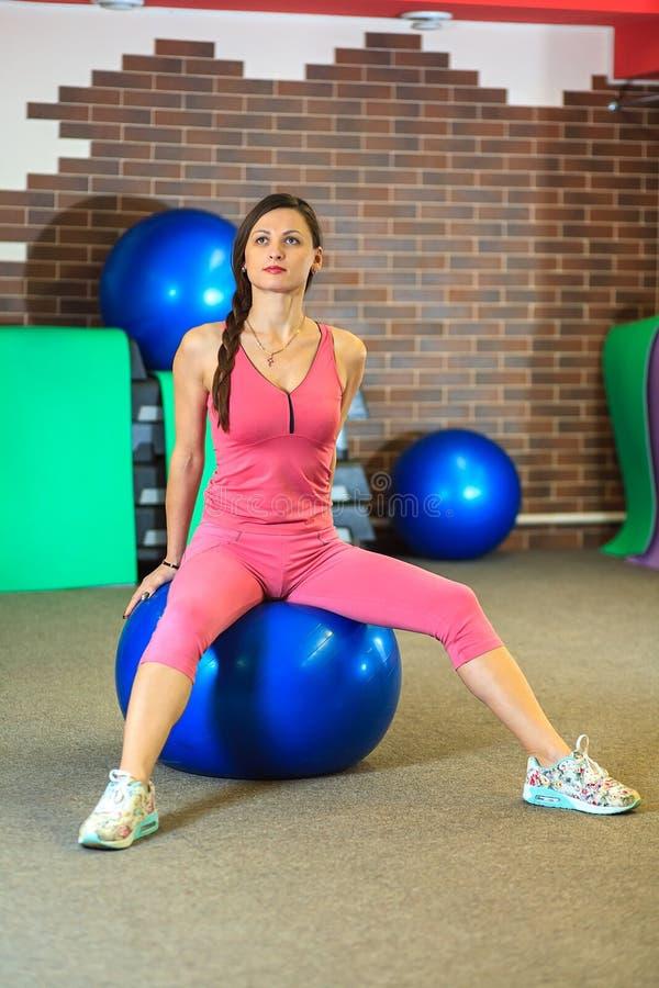 De mens van de geschiktheid training Het jonge mooie witte meisje in een roze sportenkostuum doet lichaamsbewegingen met een blau stock afbeeldingen