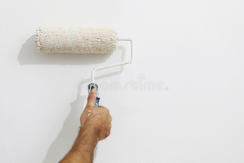 De mens van de handschilder aan het werk met een verfrol, muurschilderij royalty-vrije stock fotografie