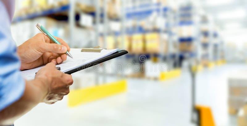 De mens van de logistiekdienst het schrijven documenten op klembord in warehous stock afbeelding