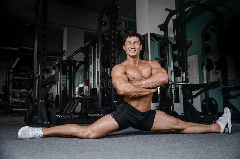 De mens van de spletenrek het uitrekken zich benen in de gymnastiek knappe geschiktheid stock foto