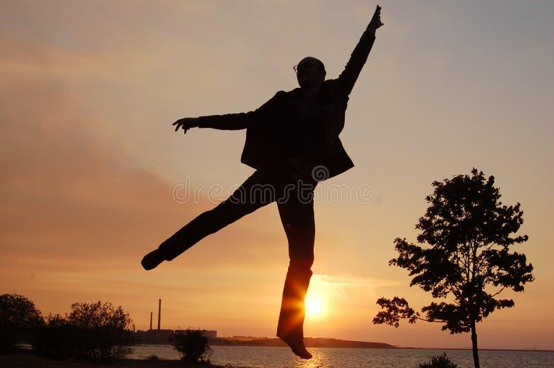De mens van de sprong op zonsondergang stock fotografie