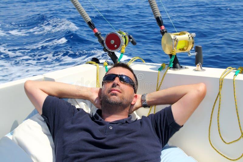 De mens van de zeeman visserij die in de vakantie van de bootzomer rust royalty-vrije stock foto