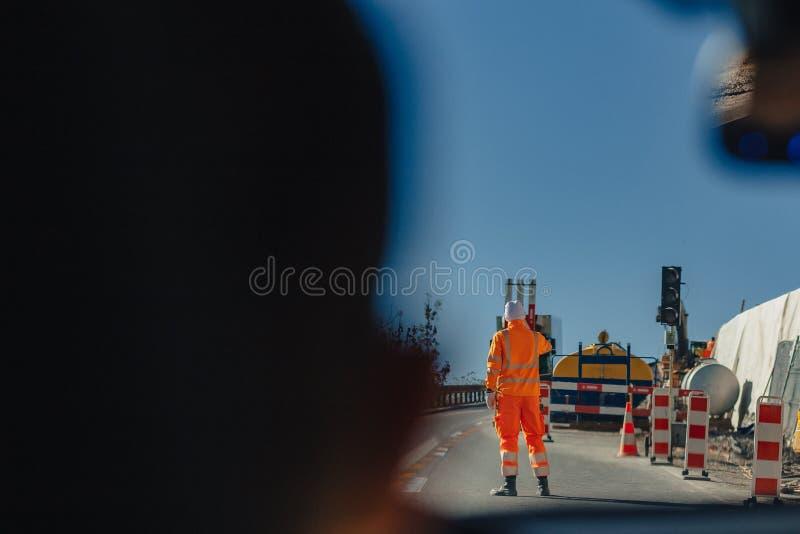 De mens van de de dienstweg in oranje jasje, Zwitserland, alpiene bergen, zonnige, blauwe hemel royalty-vrije stock foto