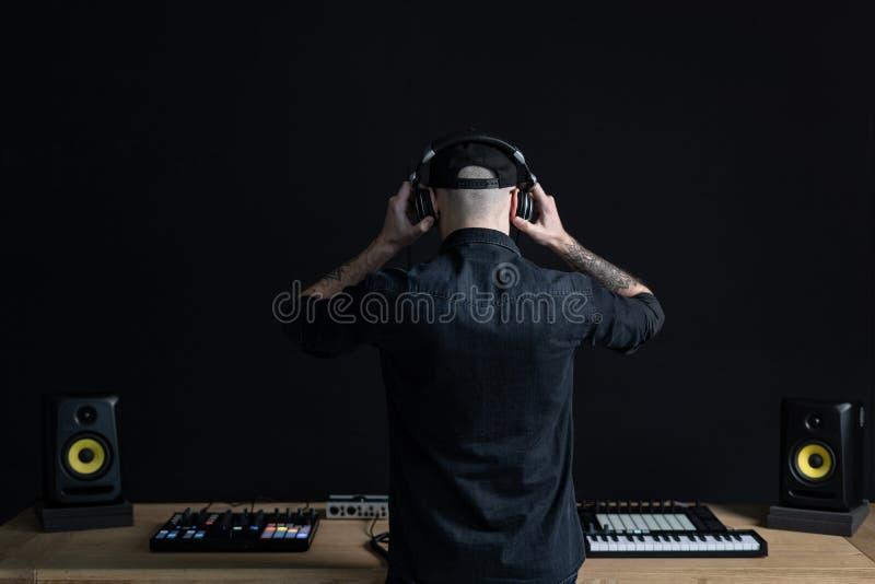 De mens van DJ creeert elektronische muziek in de studio stock afbeeldingen