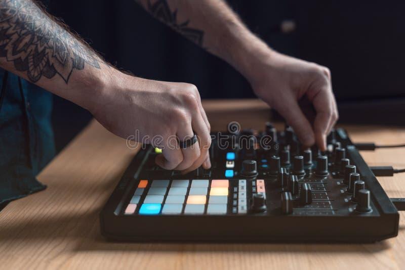 De mens van DJ creeert elektronische muziek in de studio stock foto's