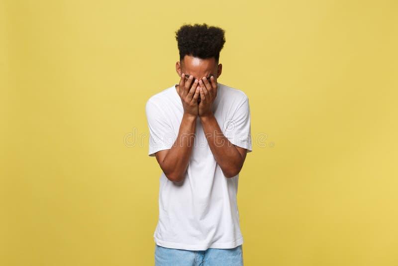 De mens van het close-upportret met droevige die uitdrukking, op gele muurachtergrond wordt geïsoleerd Menselijke emoties, kineti royalty-vrije stock foto's