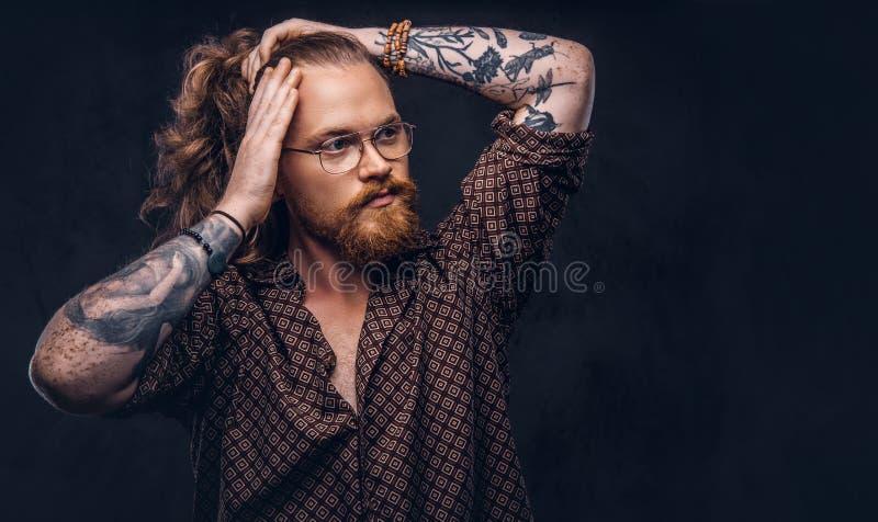 De mens van het Tattoedroodharige hipster verbetert zijn weelderig haar gekleed in een bruin overhemd, die zich bij een studio be stock afbeelding