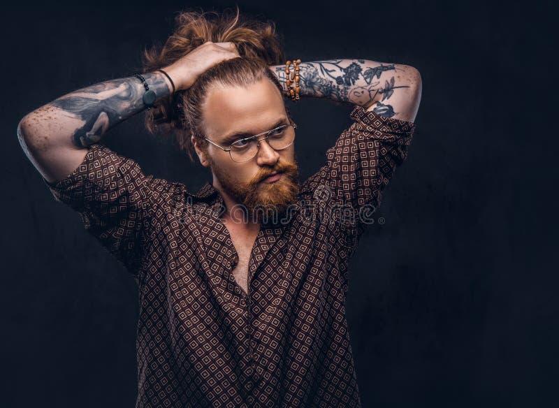 De mens van het Tattoedroodharige hipster verbetert zijn weelderig haar gekleed in een bruin overhemd, die zich bij een studio be stock foto's