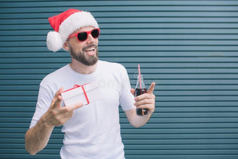 De mens van Nice bevindt zich en houdt in één hand en fles cokes in een andere huidig Ook richt de kerel met vinger royalty-vrije stock afbeelding