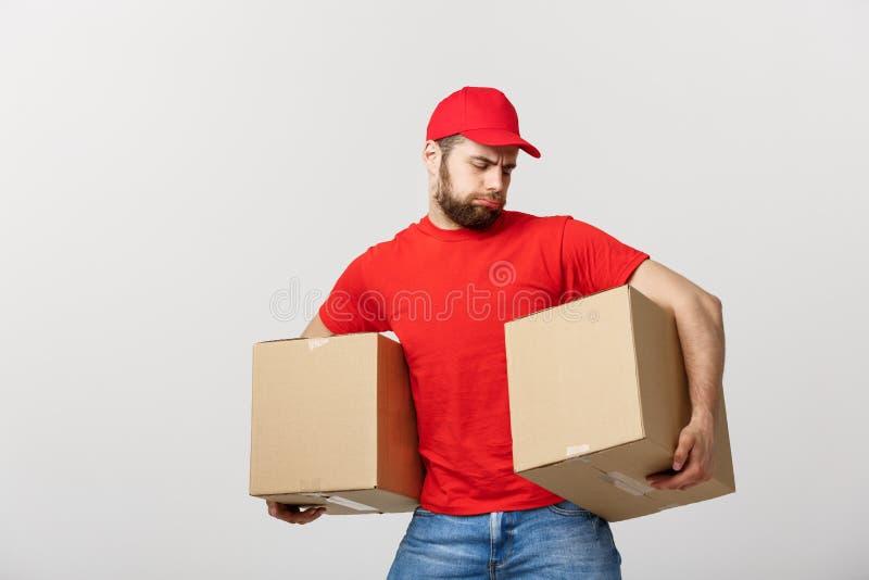 De mens van de portretlevering in GLB met rode t-shirt die als koerier of handelaar werken die twee lege kartondozen houden recei royalty-vrije stock foto