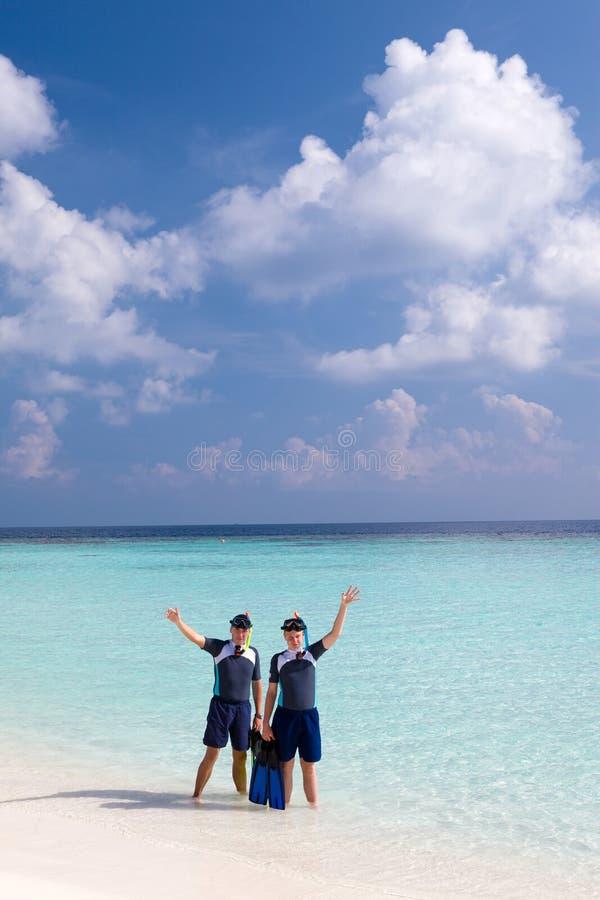 De mens van sporten en de tiener nodigen om in ocea te zwemmen uit royalty-vrije stock foto