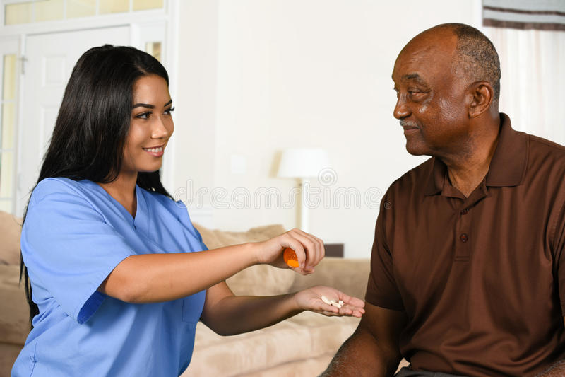 De Mens van verpleegstershelping an elderly neemt Pillen stock fotografie