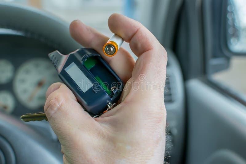 De mens verandert de batterij in het autoalarm keychain royalty-vrije stock fotografie