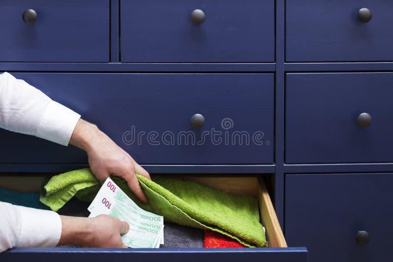 De mens verbergt een salaris in euro in een lade royalty-vrije stock afbeelding