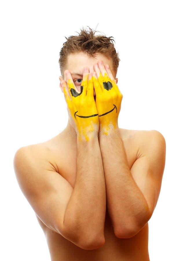De mens verbergt zijn gezicht onder glimlachmasker royalty-vrije stock foto's