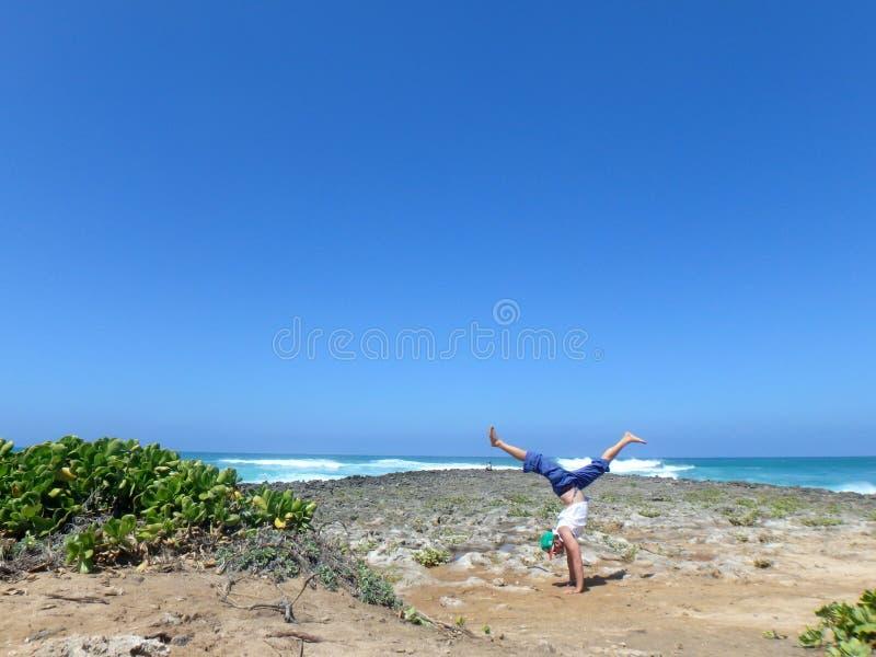De mens verdeelt beenhandstand op koraalrotsen op het strand als golf stock foto's