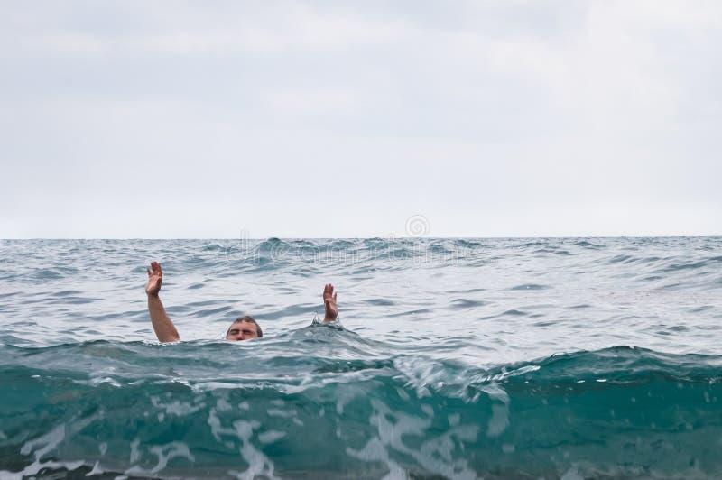 De mens verdrinkt en omhoog opheffend zijn handen royalty-vrije stock fotografie
