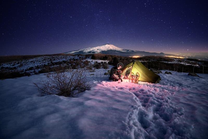 De mens verlichtte dichtbij Tent op de Sneeuw onder Sterrige Hemel stock foto