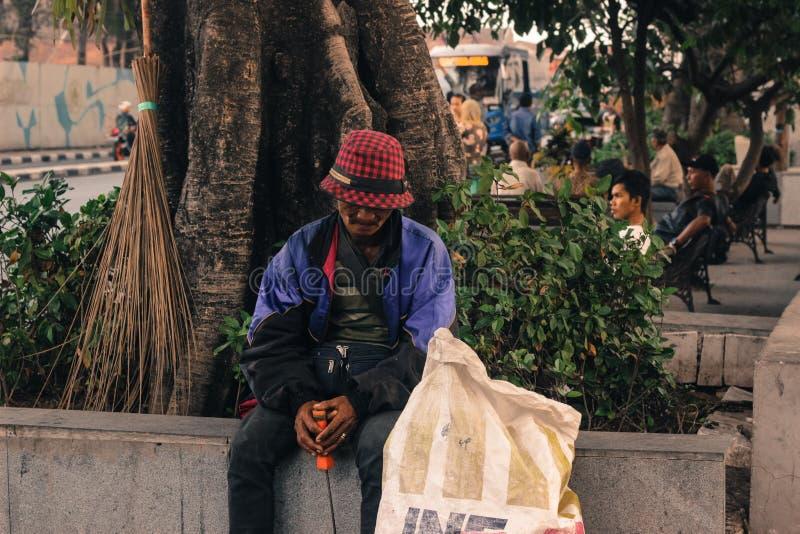 De mens verzamelt verworpen materialen Armoede en hardwork stock foto