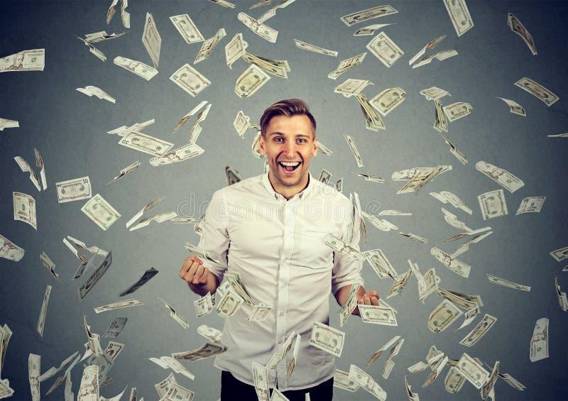 De mens viert succes onder geldregen die onderaan dollarrekeningen vallen stock afbeeldingen