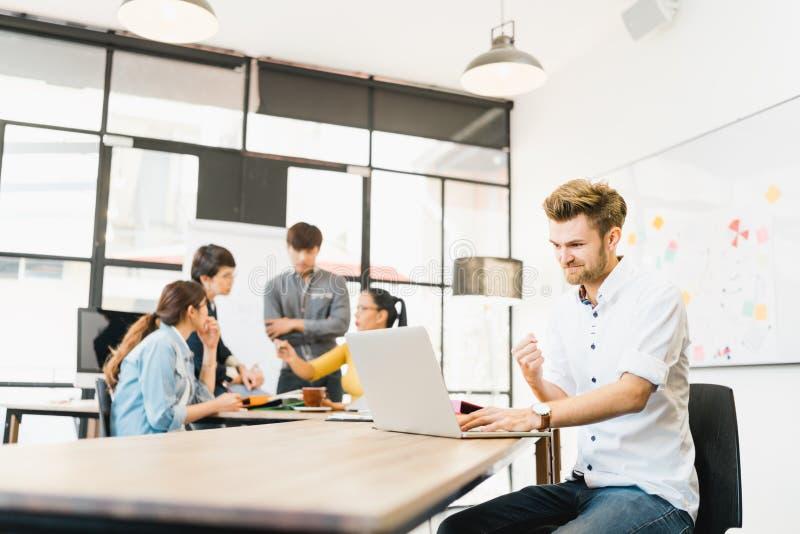 De mens viert succes stelt met multi-etnische diverse teamvergadering op kantoor Creatieve groep, bedrijfsmedewerker, of student stock fotografie