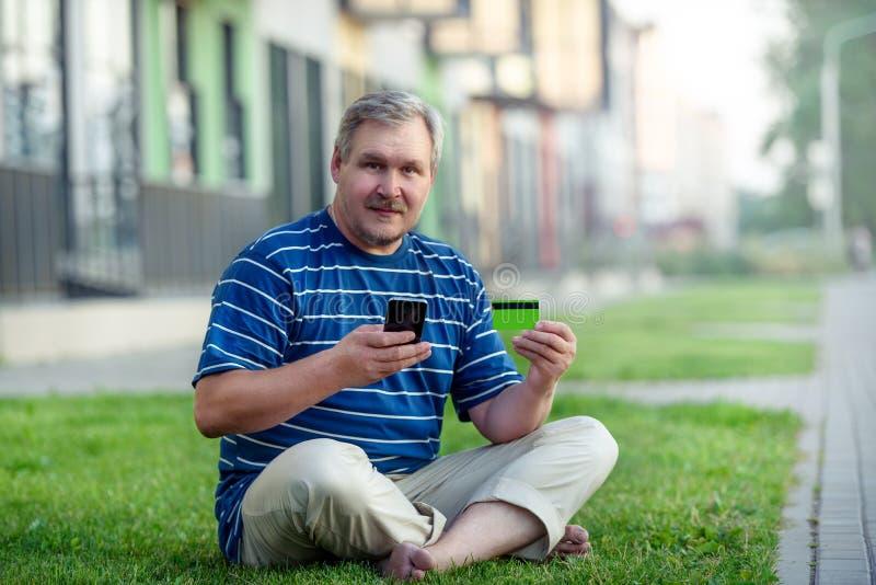 De mens vindt eommerce aanbiedingen om online met telefoon en creditcard op het stadsgazon te kopen stock afbeelding