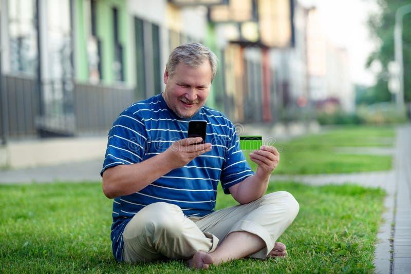 De mens vindt eommerce aanbiedingen om online met telefoon en creditcard op het stadsgazon te kopen stock afbeeldingen