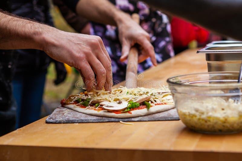 De mens voegt vullingen op zijn vers gekneed pizzadeeg toe stock foto's