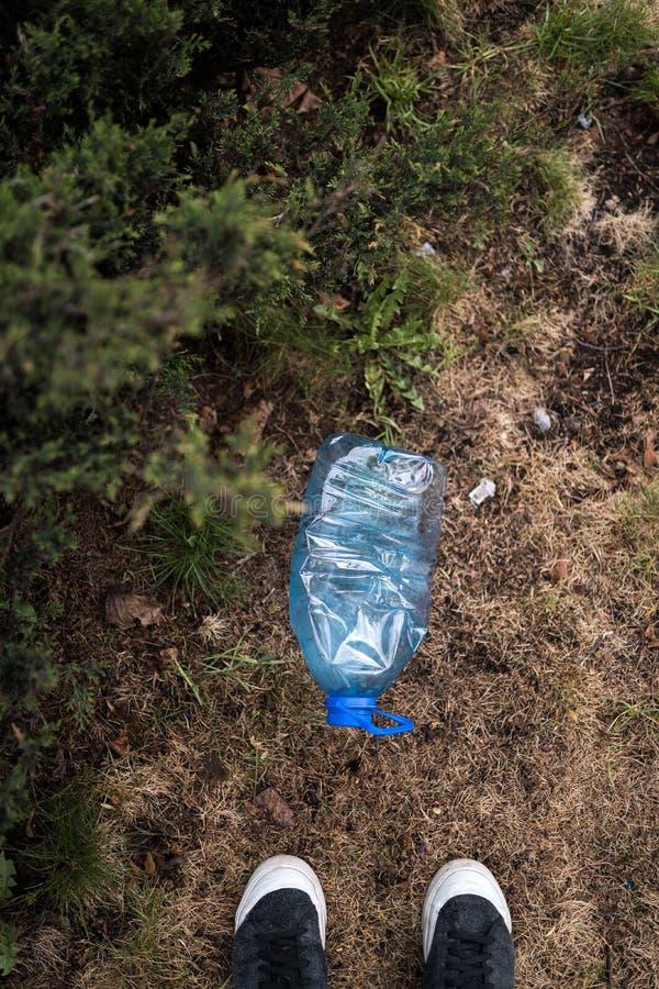 De mens vond bevindende voeten - Blauwe grote plastic fles die op de grond in boom in een Weggegooid parkbos liggen - gerecycleer royalty-vrije stock afbeeldingen