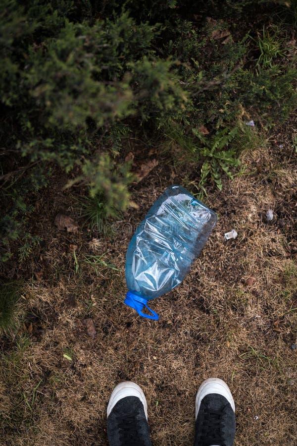 De mens vond bevindende voeten - Blauwe grote plastic fles die op de grond in boom in een Weggegooid parkbos liggen - gerecycleer royalty-vrije stock fotografie