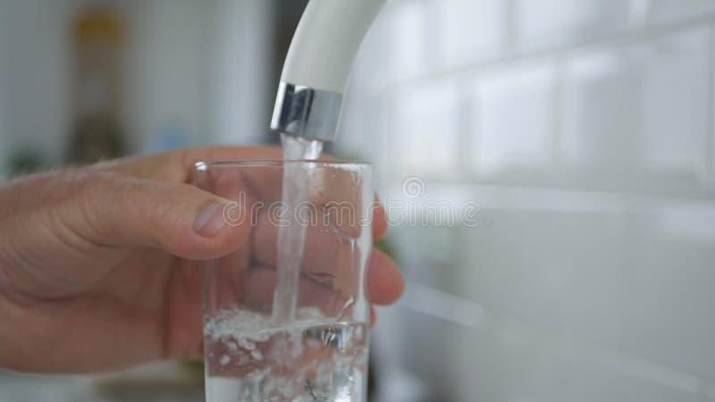 De mens vult een Glas met Zoet water van Keukentapkraan op stock fotografie