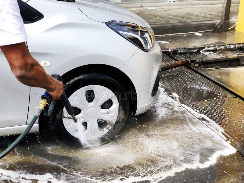 De mens wast een auto met de hand gebruikend een schuimvoorbereiding voor het oppoetsen, auto's in een carwash royalty-vrije stock fotografie