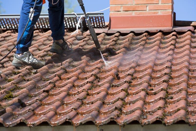 De mens wast het dak met een hoge drukwasmachine stock foto's