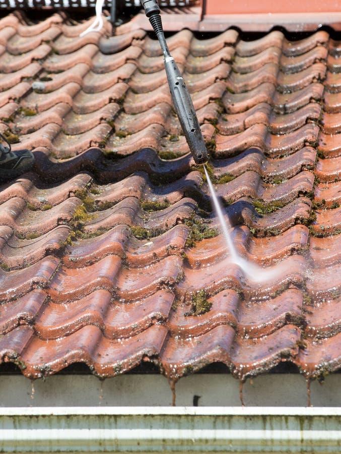 De mens wast het dak met een hoge drukwasmachine stock afbeeldingen