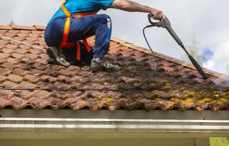 De mens wast het dak met een hoge drukwasmachine royalty-vrije stock fotografie