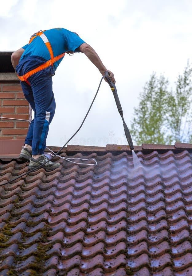 De mens wast het dak met een hoge drukwasmachine stock foto