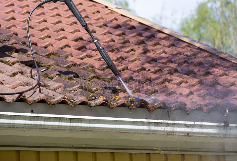 De mens wast het dak met een hoge drukwasmachine stock afbeelding