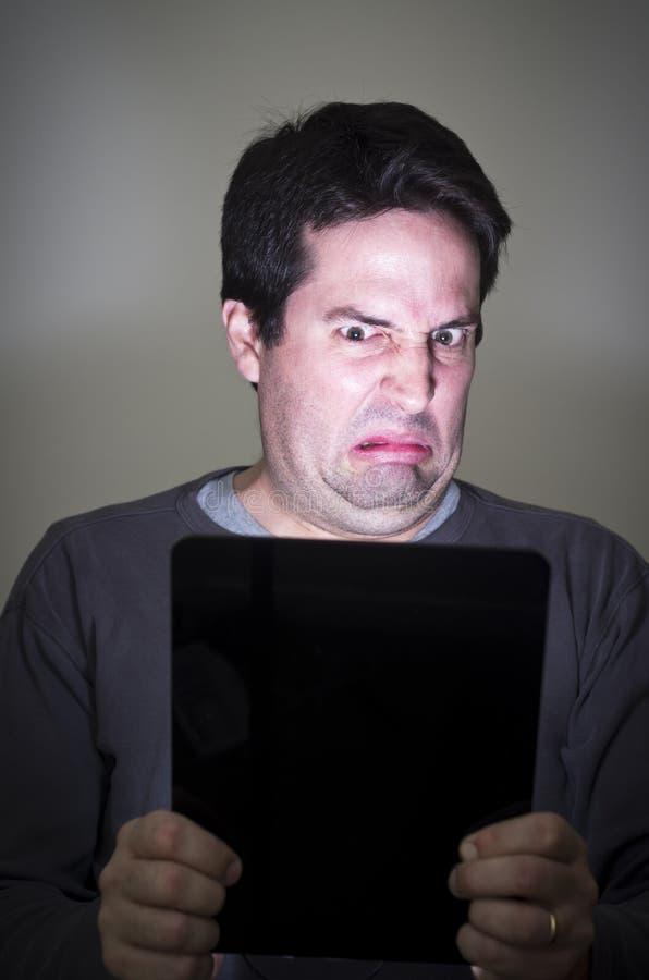De mens is weerzinwekkend door wat hij op een tabletapparaat ziet stock fotografie