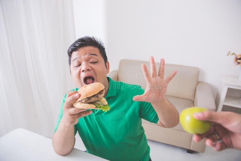 De mens weigert om gezond te eten stock afbeeldingen