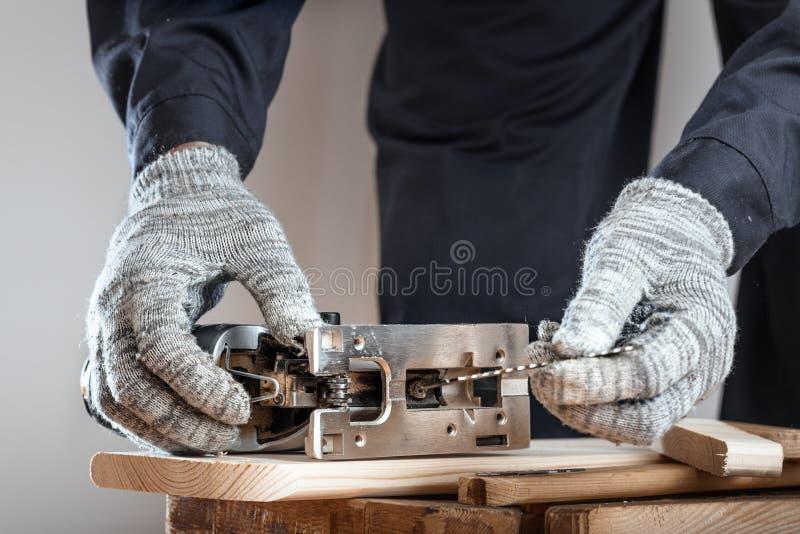De mens in werkende handschoenen vervangt de zaag in de figuurzaag Het werk concept royalty-vrije stock afbeeldingen