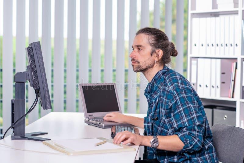 De mens werkt in zijn bureau royalty-vrije stock foto