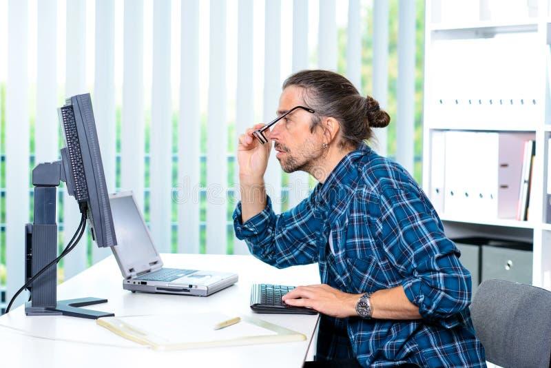De mens werkt in zijn bureau stock foto's