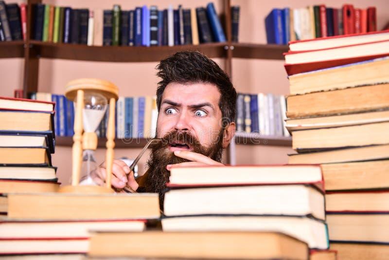 De mens, wetenschapper bekijkt zandloper De mens op ernstige en geschokte gezicht het letten op tijd gaat over, boekenrekken stock foto