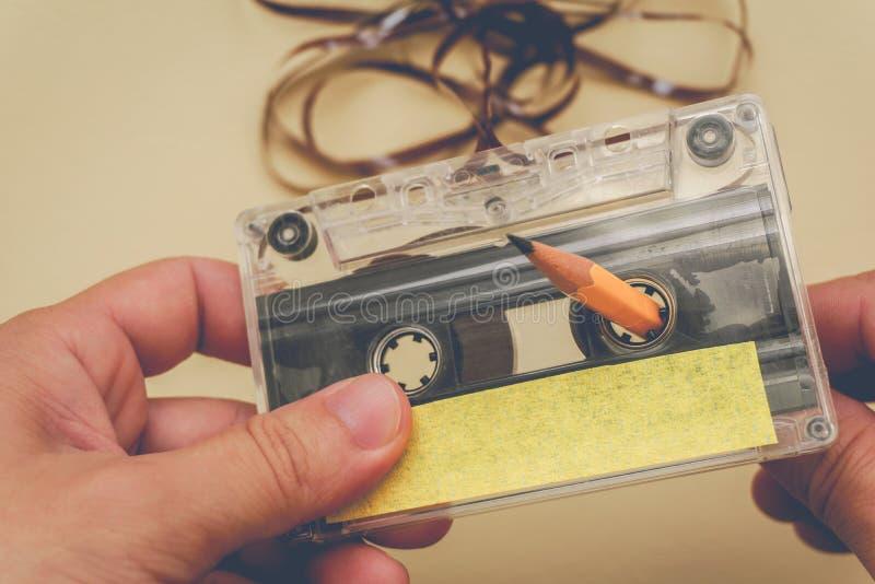 De mens windt een cassetteband opnieuw op stock afbeeldingen