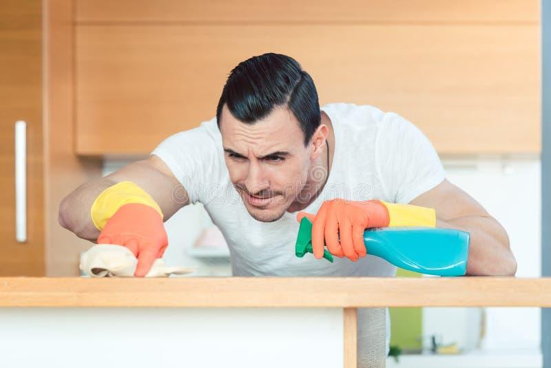 De mens is zeer het ijverige bestrooien van en het schoonmaken van de keuken royalty-vrije stock afbeeldingen