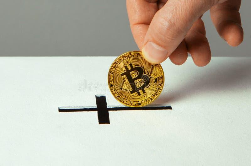 De mens zet bitcoin schenking in de groef in de vorm van Christelijk kruis stock afbeelding