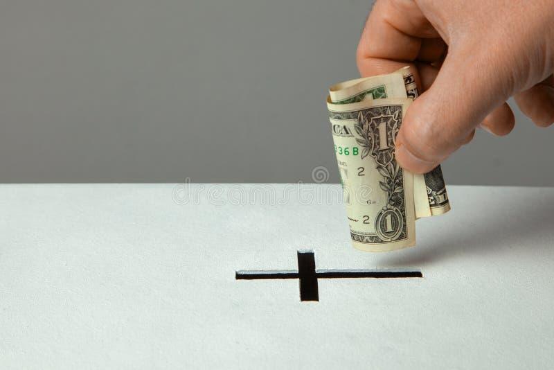 De mens zet schenking in zijn hand met dollar in groef in de vorm van Christelijk kruis Exemplaarruimte voor tekst stock fotografie