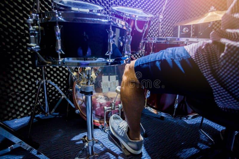 De mens zette witte sportschoenen en spelend het drumstel en de baarzen trommel met voet in muziekruimte royalty-vrije stock foto's