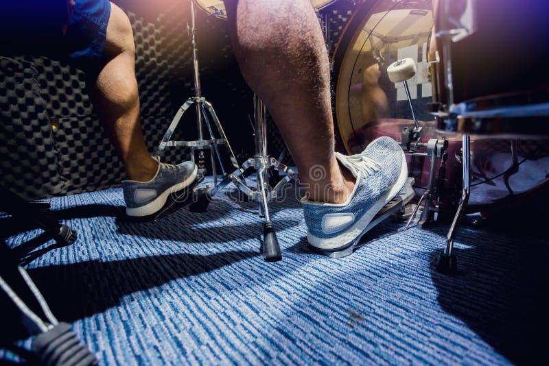 De mens zette witte sportschoenen en spelend het drumstel en de baarzen trommel met voet in muziekruimte stock fotografie